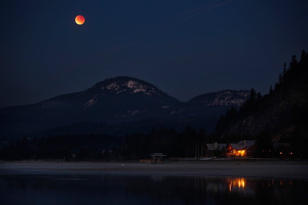 Orange moon over cabin and mountain