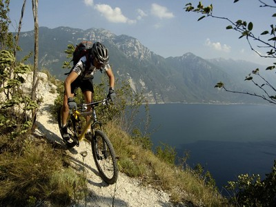 person mountain biking in front of lake and mountains