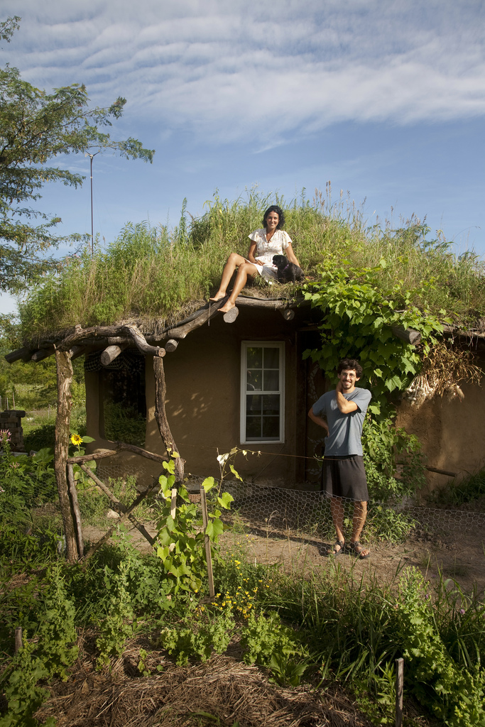 couple built a cob house for themselves with the woman on the rooftop with her dog