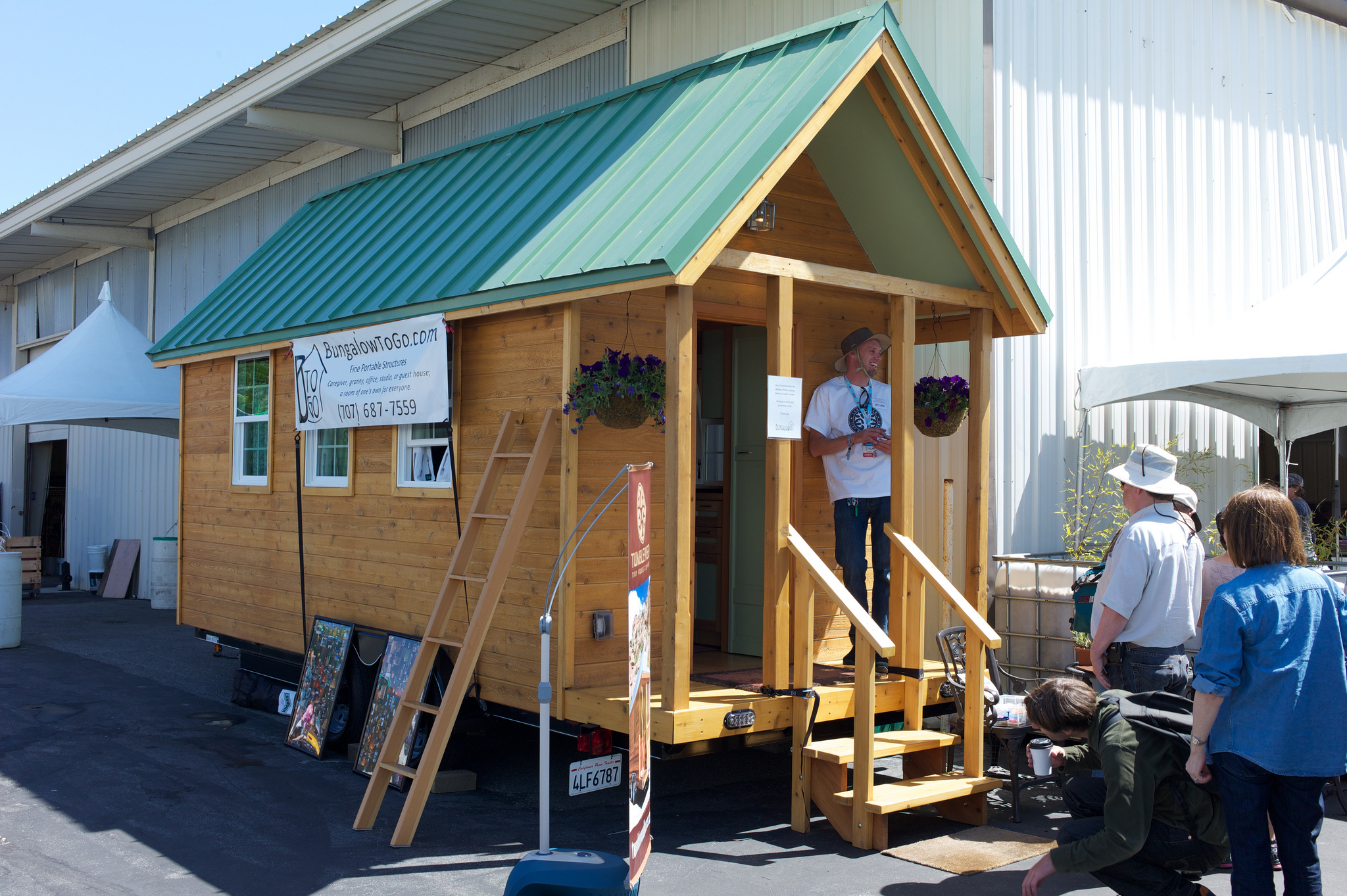 people looking at how a tiny house on wheels looks like