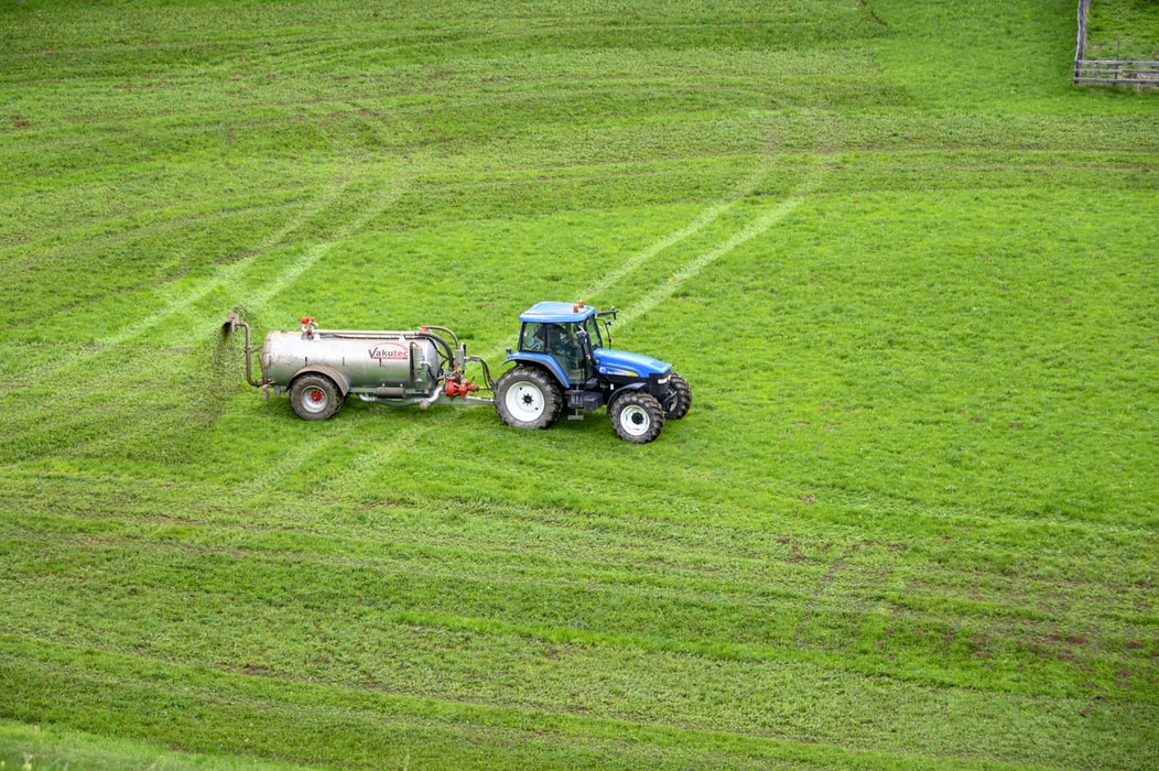 tractor with large container flushing fertilizers on field